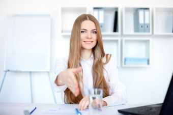Portrait of beautiful young smiling business woman sitting at de