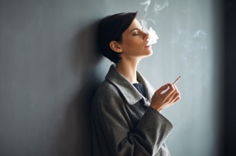 Portrait of fashionable woman smoking a cigarette on dark backgr
