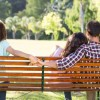 Lonely woman sitting with couple in park on a sunny day